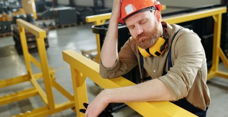 Tired male worker in hard hat leaning on railing on a factory floor.