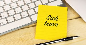 Sick leave written on a sticky note next to a keyboard and pen.